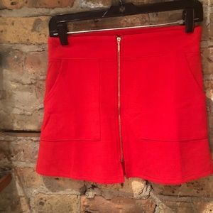 Bright coral mini skirt with gold zipper detail